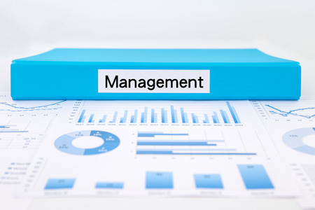 administration: Blue document binder with management word place on graph analysis of evaluation report concept for business strategic planning