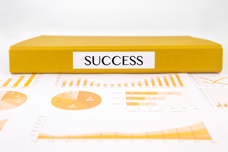 Yellow document binder with success word place on graphs, charts and business reports
