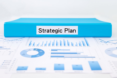 Blue document binder with strategic plan word place on graph analysis and evaluation report