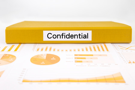 그래프 분석, 차트 및 미공개 보고서에 기밀 단어 장소 노란색 문서 바인더