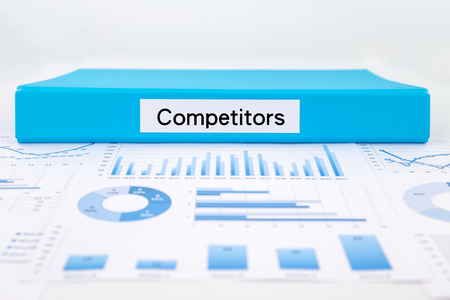 competitors: Blue document binder with competitors word place on graph analysis, concept for business strategic planning Stock Photo