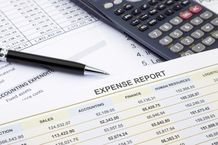 Business expense report with pen and calculator