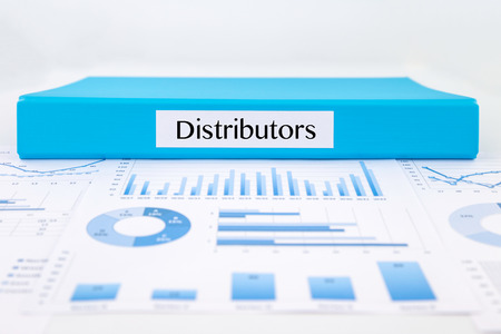 distributor: Blue document binder with Distributors word place on graphs analysis and marketing reports