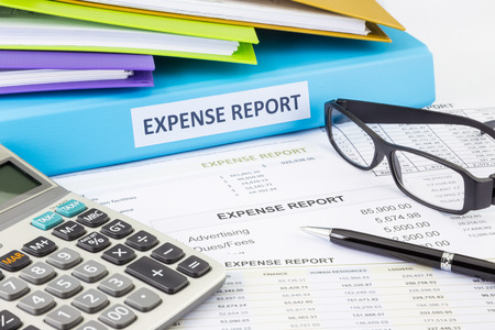Business expense report binder with financial documents and calculator Foto de archivo