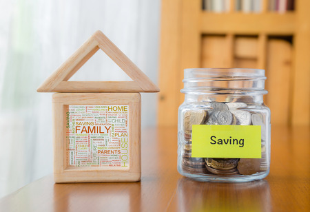Saving label on money jar and wooden home  blocks with house and family word cloud