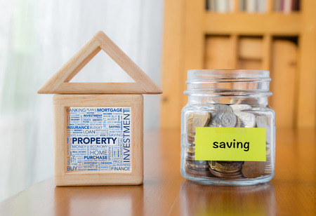 Saving label on money jar and wooden home  blocks with investment property word cloud