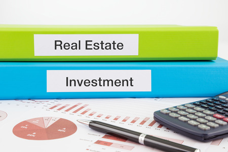 Real Estate and Investment words on labels with document binders, graphs and business reports