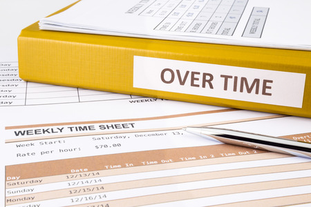 payroll: Overtime words on document binder place on blank weekly time sheets