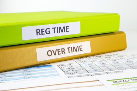 timekeeping: Regular time and Over time words on labels, document binders place on employee time sheets Stock Photo