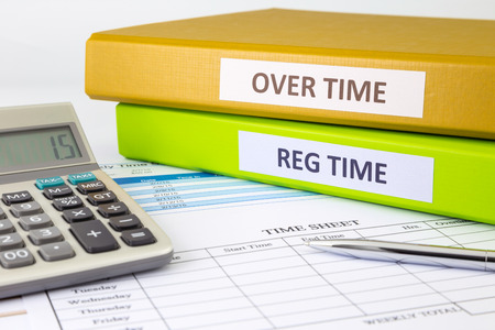 timekeeping: Regular time and Over time words on labels, document binders place on blank payroll time sheets