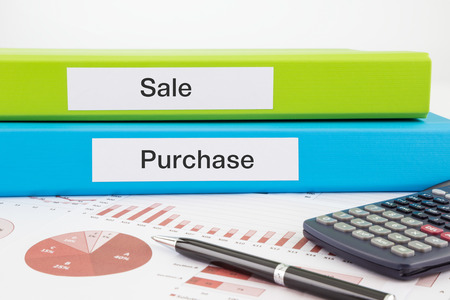 Sale and Purchase words on labels with document binders, graphs and business reports