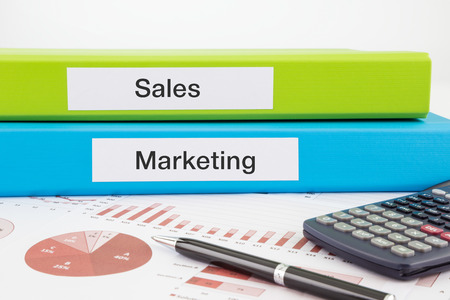 Sales and Marketing words on labels with document binders, graphs and business reports