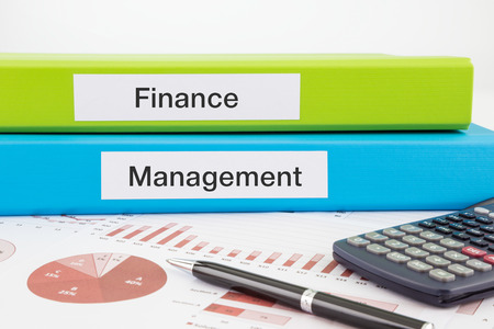 Finance and Management words on labels with document binders, graphs and business reports