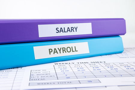 binders: PAYROLL and SALARY word on binder place on weekly time sheet documents, human resources concept Stock Photo
