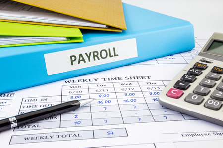 binders: PAYROLL word on blue binder place on weekly time sheet and payroll summary report, human resources concept Stock Photo