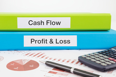 profit and loss: Cash Flow, Profit & Loss words on labels with document binders, graphs and business reports Stock Photo