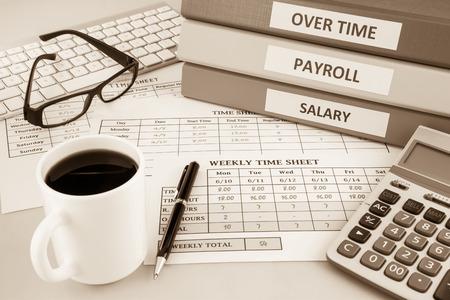 인적 자원 문서 : 급여, 급여 및 직원 시간 시트는 커피와 계산기, 세피아 톤의 컵 사무실 테이블에 배치