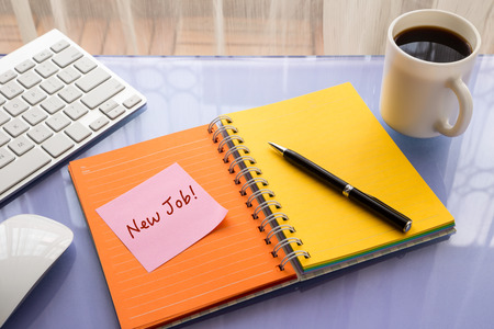 reminder concept: New job word on note pad stick on blank colorful paper notebook at workspace, reminder concept Stock Photo