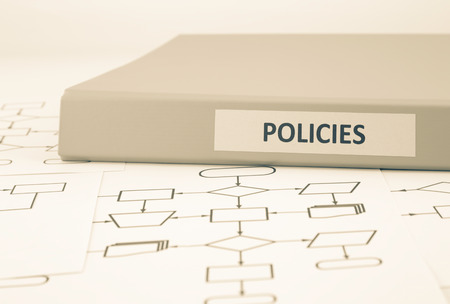 Business document binder with POLICIES word on label place on blank process procedure flow charts, sepia tone image Фото со стока