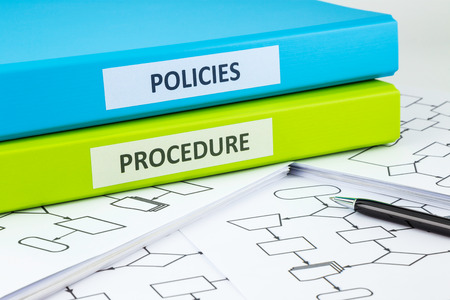 Document binders with POLICIES and PROCEDURE words on labels place on blank process flow charts with pen photo
