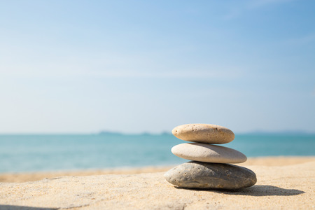 Stones balance, pebbles stack on the sand beach with shadow on right side , beautiful sea view during daytime on a sunny day with blue sky on background Stock Photo