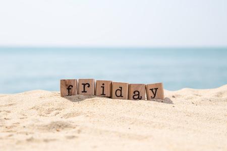 背景、日と時間の概念に美しい青い海の景色と砂浜のビーチに木製のゴム印スタック上の金曜日の単語