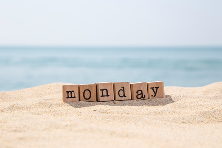 Monday word on wood rubber stamps stack on sunny beach with beautiful blue ocean view on background, day and time concepts