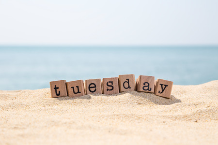 Tuesday word on wood rubber stamps stack on seaside with beautiful blue sea view on background, day and time concepts Stock Photo