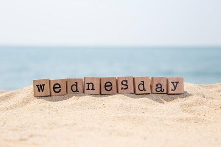 背景、日と時間の概念に美しい青い海を望む日当たりの良い海岸に木製のゴム印スタック上の水曜日の単語