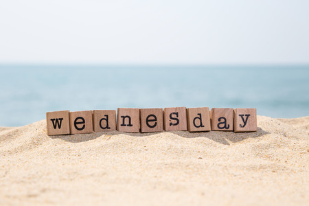 Wednesday word on wood rubber stamps stack on sunny beach with beautiful blue ocean view on background, day and time concepts