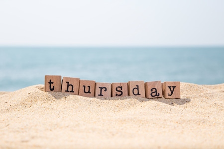 thursday: Thursday word on wood rubber stamps stack on sand and seaside with beautiful blue ocean view on background, day and time concepts