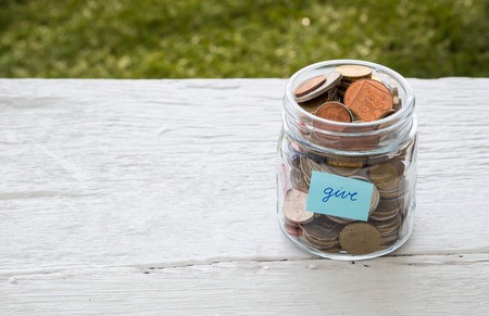 World coins in money glass jar with blue GIVE word label place on white wood table, blank space for text,  donation and charity concept