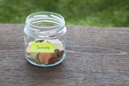 World coins in money glass jar with DONATE word label place on natural wood table, blank space for text