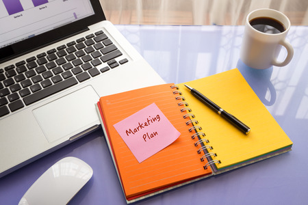 notebook: Message on paper with Marketing Plan word on note stick on colorful book with laptop and a cup of coffee on glass table, top view image