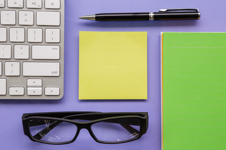 Blank yellow notepad putting on office table  with pen, keyboard, book and glasses sort orderly Stock Photo