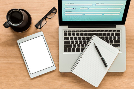 diary: Open laptop shows blank information form and  digital tablet with isolate screen on wooden table. Blank diary book and pen on laptop, glasses and a cup of coffee on workspace. Top view image for mock up concept. Stock Photo