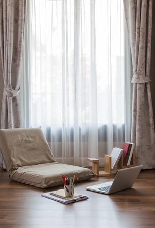 太陽の光でリビング ルームの大きな窓は、薄い白のカーテンを通ってくる。折り畳み怠惰な椅子、ノート パソコン、書籍階文房具と自宅でオンライ