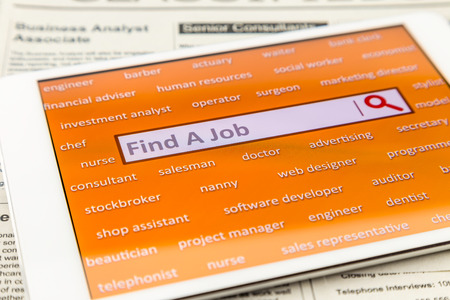 find a job: Orange tablet screen fill with difference career words.  Internet website for online job search having wording find a job and searching symbol in search engine box. Blur classifieds ads on background.