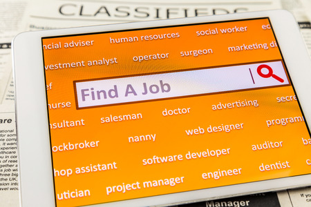 job engine: Orange tablet screen fill with difference career words. Internet website for online job search having wording find a job and searching symbol in search engine box. Blur classifieds ads on background. Top view image.