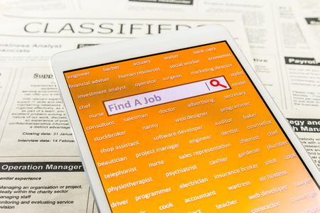 classifieds: Orange tablet screen fill with difference career words. Internet website for online job search having wording find a job and searching symbol in search engine box. Blur classifieds ads on background. Bird eye view image.