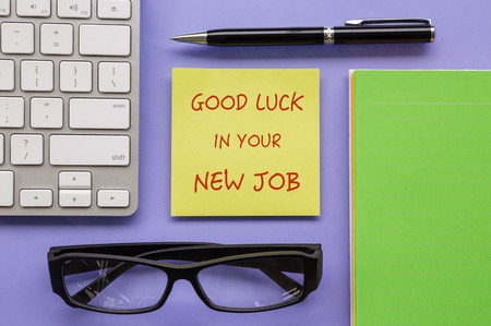 """Bovenaanzicht van gele notitieblok met woorden  """"Good Luck in uw nieuwe baan """" zetten op werkruimte met pen, toetsenbord, papieren boek en glazen soort ordelijke"""