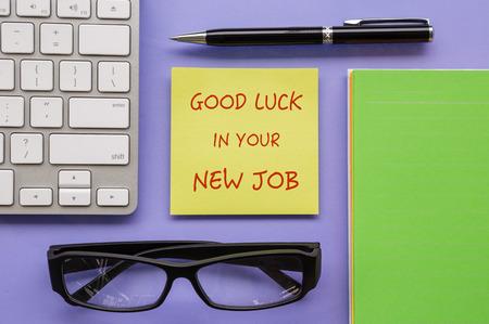 """buena suerte: Vista superior de bloc de notas amarillo con las palabras  """"Buena suerte en su nuevo trabajo """" poner en espacio de trabajo con la pluma, teclado, libro de papel y gafas tipo ordenadas Foto de archivo"""