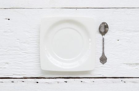 dessert plate: Vista dall'alto del piatto di ceramica bianca quadrata da dessert e vintage cucchiaino mettere sul tavolo di legno vecchio.
