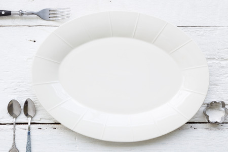 kitchen table top: Top view of empty oval ceramic dish, fork, teaspoons and flower shape cookie cutter putting on white wooden table. retro, vintage and country style image