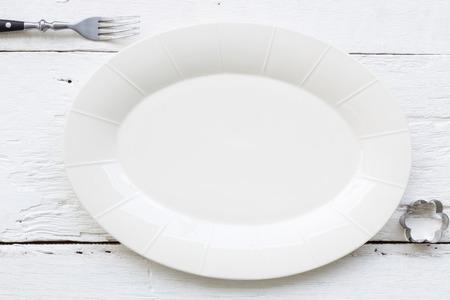stile country: Vista dall'alto del piatto in ceramica ovale vuoto, forchetta e forma di fiore cookie cutter mettendo sul tavolo in legno bianco. retro, immagine d'epoca e stile country