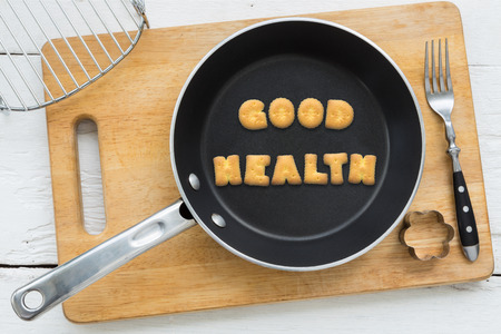 putting in: Top view of alphabet collage made of biscuits. Word GOOD HEALTH putting in black pan. Other kitchenware: fork cookie cutter and chopping board putting on white wooden table vintage style image.