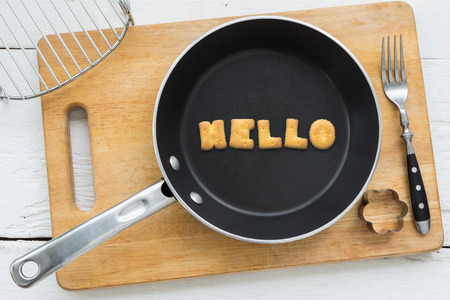putting in: Top view of alphabet collage made of biscuits. Word HELLO putting in black pan. Other kitchenware: fork cookie cutter and chopping board putting on white wooden table vintage style image. Stock Photo