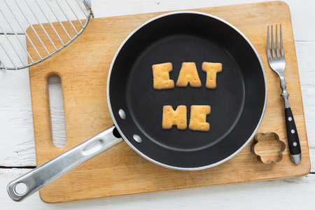 putting in: Top view of letter collage made of biscuits. Word EAT ME putting in black frying pan. Other cooking equipments: fork cookie cutter and chopping board putting on white wooden table vintage style image.