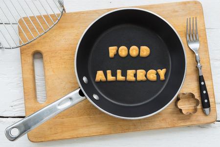 ビスケットの手紙コラージュの平面図です。黒いフライパンに入れて単語食物アレルギー。その他の調理機器: 白い木製テーブル ビンテージ スタイ