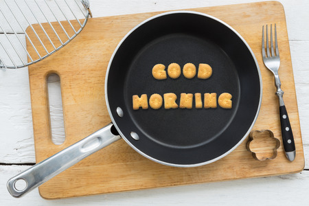 putting in: Top view of letter collage made of biscuits. Word GOOD MORNING putting in black frying pan. Other cooking equipments: fork cookie cutter and chopping board putting on white wooden table vintage style image.